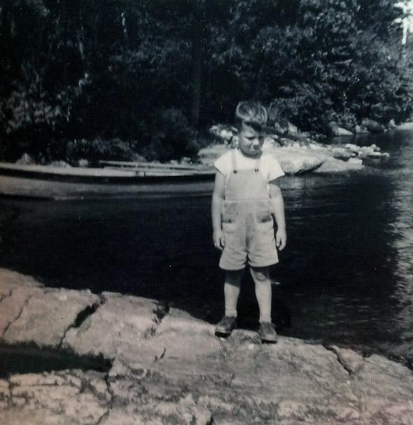 little boy standing on a shore